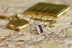 Antiques gold stillife. Antiques amethyste golden ring with flower decor and diamonds, golden pocket watch, chain and cigarette case on light marble stock images