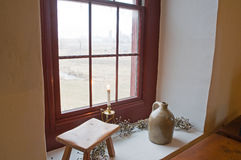 Antiques on old windowsill. A view looking across a field out of an old window with antiques on a large windowsill Royalty Free Stock Photos