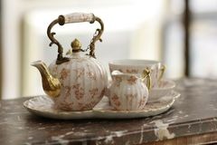 Antiques china tea set on marble. Antiques porcelain tea set with pink printed angel and flower decor on dark marble table royalty free stock images