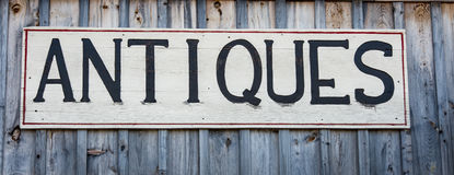 Antiques sign. Wooden antiques sign on a wood background in New England stock photo