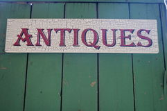 Antiques Wood Sign. Maroon Red Antiques sign on wood. Spells out Antique, with turquoise wood background Stock Images