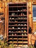 Antiquitäten, die an den hölzernen Scheunenwandregalen, künstlerisch, rustikal hängen lizenzfreies stockfoto
