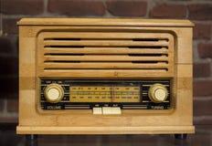 Antiquiteit; retro houten radio op de rode achtergrond van de steenmuur Antieke radio stock afbeeldingen