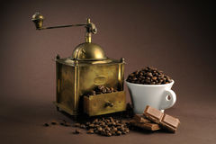Antiquity coffee machine. With beans over brown background Stock Photos