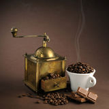 Antiquity coffee machine. With beans over brown background Stock Photo