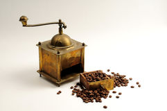Antiquity coffee machine. With beans over white Royalty Free Stock Photography