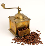 Antiquity coffee machine. With beans over white Royalty Free Stock Images