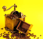 Antiquity coffee machine. With beans over yellow background Royalty Free Stock Photography