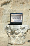 Antiquity meeting new technologies. Laptop with picture of greek amphitheatre standing on the flat carved stone. Cyprus Royalty Free Stock Photography