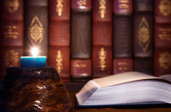 Antiquity - reading old books with candle light Stock Photos