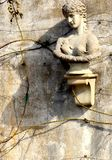 Antiquity Is Theme of Strange Wall Statue and Bare Rose Stems With Thorns stock photos