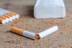 Antirauchenhintergrund mit defekter Zigarette auf Holzoberfläche Stockbild