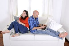 Antisocial latin couple while on laptop and tablet. Antisocial latin couple sitting on sofa in living room being addicted to technology working on computer and stock image