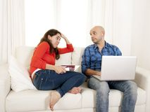 Antisocial latin couple while on laptop and tablet. Antisocial latin couple sitting on sofa in living room being addicted to technology working on computer and royalty free stock photography