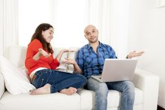 Antisocial latin couple while on laptop and tablet. Antisocial latin couple sitting on sofa in living room being addicted to technology working on computer and stock photo