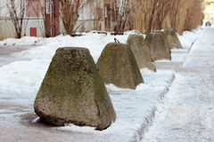 Antiterrorist pyramidal concrete pedestals near the house beside the road against the entry of vehicles. Relevant when the danger. Of terrorist attacks Royalty Free Stock Photos