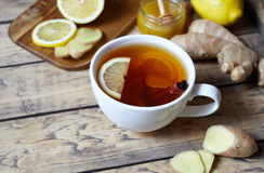 Antiviral ginger tea with lemon and honey on wooden background. Healthy drink. Rustic style. Creative composition. Stock Photos