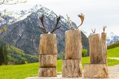 Antler Chairs with mountain background. These chairs have antlers on their backs and make for a perfect picture with the mountains as a backdrop. The warm light stock photo