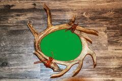 Antler horn tied with leather round frame on rustic wood background with greenscreen opening - room for copy