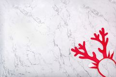 Antlers of a deer headband on marble background. Pair of toy reindeer horns. Red antlers of a deer headband on marble background. Pair of toy reindeer horns on royalty free stock photos
