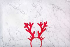 Antlers of a deer headband on marble background. Pair of toy reindeer horns. On white marble texture stock photo