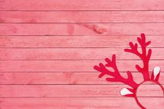 Antlers of a deer headband on pink wooden background. Toy reindeer horns on pink wooden texture. Top view. Flat lay stock photos