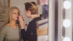 Antlitz - Maskenbildner und blonder vorbildlicher naher Spiegel in der Umkleidekabine Lizenzfreies Stockfoto
