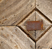 Antonino abstract samarate   rusty brass brown knocker. Santo antonino abstract samarate   rusty brass brown knocker in a  door curch  closed wood lombardy italy Royalty Free Stock Photos