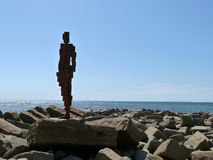 Antony Gormley Iron man sculpture Kimmeridge Bay, Dorset. Cast-iron, life size sculpture of a man staring out to sea taken into the sun to produce a vivid image Royalty Free Stock Image