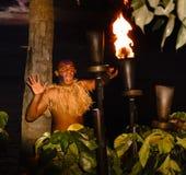 Antorcha del tiki de la iluminación del guerrero del Fijian en la puesta del sol Fotos de archivo
