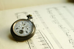 Antque Pocket Watch On Music. Antique pocket watch laying on music sheet background Stock Photo