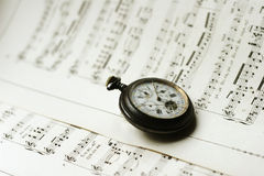 Antque Pocket Watch On Music Sheets. Antique pocket watch laying on music sheet background Stock Photos