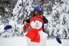 Antreiben in einen Schlitten Mädchen in einer Strickmütze sculpts einen Schneemann Stockfotografie