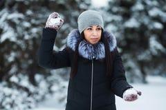 Antreiben in einen Schlitten Nette junge Frau, die mit Schnee in den warmen woolen Handschuhen und im Mantel im Winterpark spielt stockfoto
