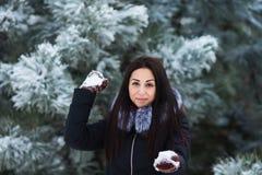 Antreiben in einen Schlitten Nette junge Frau, die mit Schnee in den warmen woolen Handschuhen und im Mantel im Winterpark spielt stockfotografie
