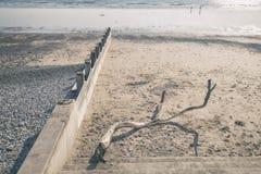 Antrieb-hölzerne Niederlassung und Wellenbrecher auf Sandy Beach Lizenzfreie Stockfotografie