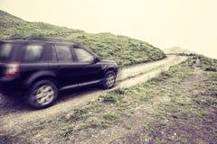 Antriebe des Autos 4x4 über Spitzen Stockfotografie