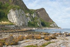 Antrim Coast. Typical view of the scenic Antrim coast in Northern Ireland. The rocky outcrop of the headland shows clearly the sedimentary formation of the stock photography