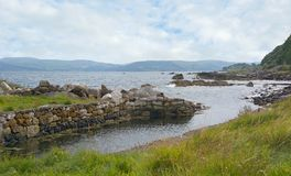 Antrim Coast. Typical view of the scenic Antrim coast in Northern Ireland. A dry stone wall forms a little harbor, sunshine sparkles on an inlet of the Irish Sea royalty free stock photography
