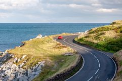 Antrim Coastal Road in Northern Ireland, UK. The eastern coast of Northern Ireland and Antrim Coastal Road, a.k.a. Causeway Coastal Route with a red car in royalty free stock image