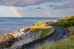 Antrim Coastal Road and rainbow in Northern Ireland, UK. The eastern coast of Northern Ireland and Antrim Coastal Road, a.k.a. Causeway Coastal Route with cars royalty free stock photography