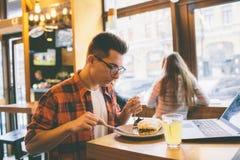 Antropófago en un restaurante y el goce de la comida deliciosa Imagenes de archivo