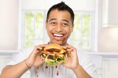 Antropófago joven feliz una hamburguesa grande Imágenes de archivo libres de regalías