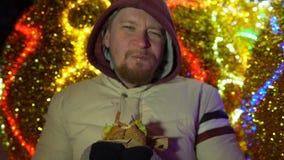 Antropófago novo um Hamburger na rua ao lado das luzes de Natal festivas video estoque