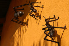 Ants closeup. Row of metallic handcrafted ants attached to an orange colored wall royalty free stock images