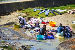 African women washing clothes on a river. ANTSIRABE, MADAGASCAR, SEPTEMBER 2014, Unknown african women washing clothes on a river. Washed clothes are lied down Stock Photography