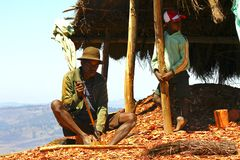 Hard working poor malagasy man - poverty. ANTSIRABE, MADAGASCAR, SEPTEMBER 2014, Unknown malagasy man working hard with wood- poverty royalty free stock images