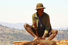 Hard working poor malagasy man - poverty. ANTSIRABE, MADAGASCAR, SEPTEMBER 2014, Unknown malagasy man working hard with wood- poverty stock images