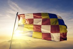 Antwerp Antwerpen Province of Belgium flag textile cloth fabric waving on the top sunrise mist fog. Beautiful royalty free stock image