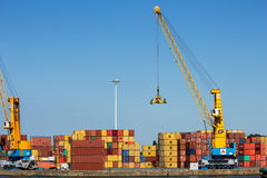 Harbor gantry cranes and sea containers stock images